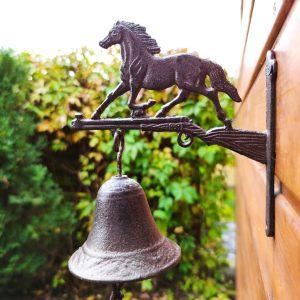Żeliwny dzwon z figurą galopującego konia.