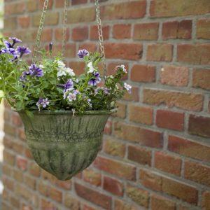 wisząca doniczka z postarzanego metalu w kształcie kosza z kwiatami